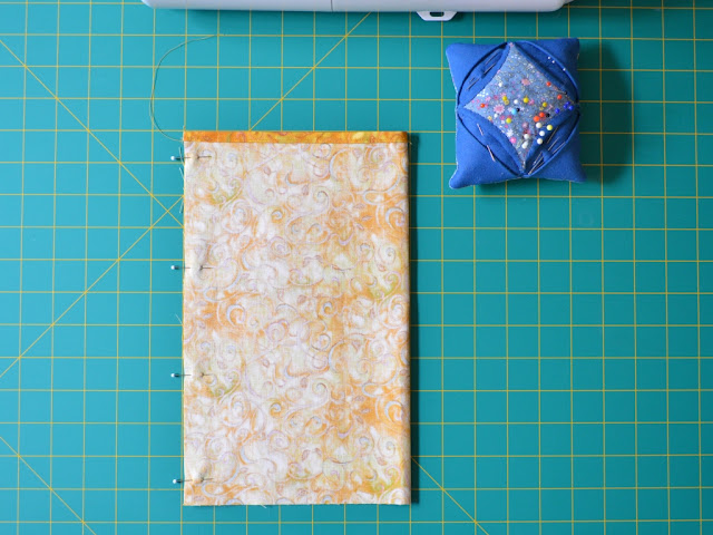 The folded fabric is laid out on the cutting mat grid. The straight side edges meet on the right hand side. They are pinned together with glass head pins, ready for seaming.  The blue pincushion and white base of the sewing machine can be seen towards the top of the photo.