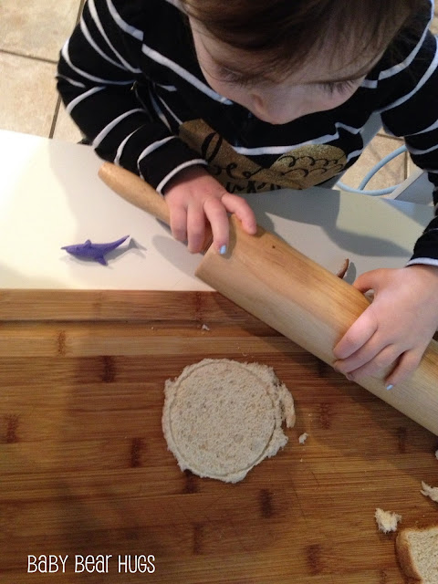 little girl rolling dough with a rolling pin