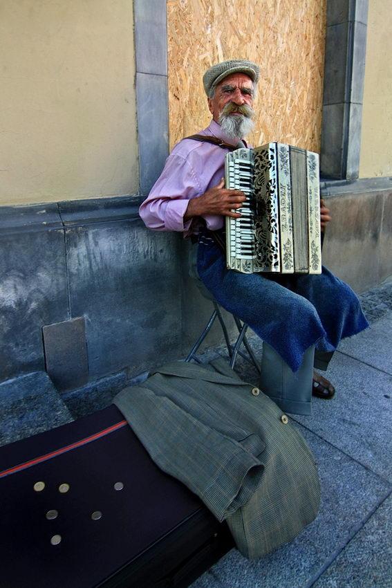 Tocador de acordeão em plena rua com algumas moedas em cima duma mala.