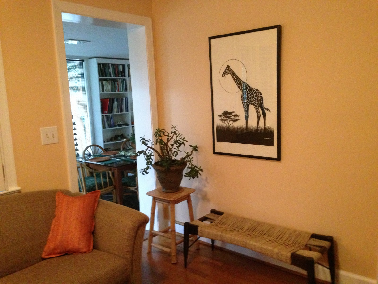 Giraffe painting with black frame provides nice contrast to wall color  title=
