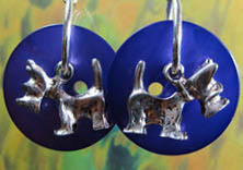 Big drop dangle earrings have silver puppy charms layered on striking blue buttons
