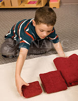 boy working on montessori practical life activity folding autism autistic children montessori works