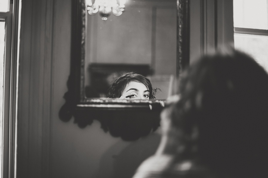 Bridge applying mascara in the mirror, only her eye is visible