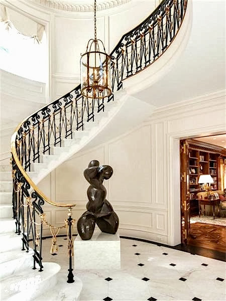 Grand foyer in a Palm Beach estate with marble floor, a large modern sculpture and winding staircase with gold and black railing