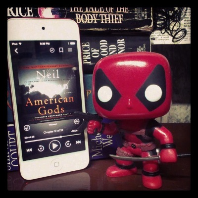 Tiny Deadpool, a four-inch tall bobblehead dressed in a red and black bodysuit and brandishing a gun and a katana, stands beside a red-bordered iPod with the cover of American Gods on its screen. The cover features a burst of bright light in a cloudy sky. The iPod is propped up against a stack of books by Anne Rice, Elizabeth Willey, K.J. Parker, and Michelle West.