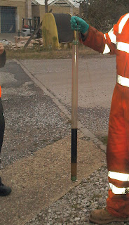 Technician holds bailer sample from borehole contaminated with hydrocarbons