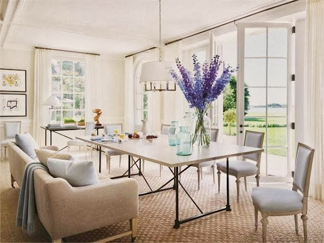 Elegant and inviting dining room in Villa Maria with french doors, carpeted floor, white pendant light and a sofa