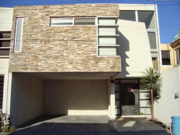 casa con fachada de revestimiento de piedra y ventanas contemporáneas