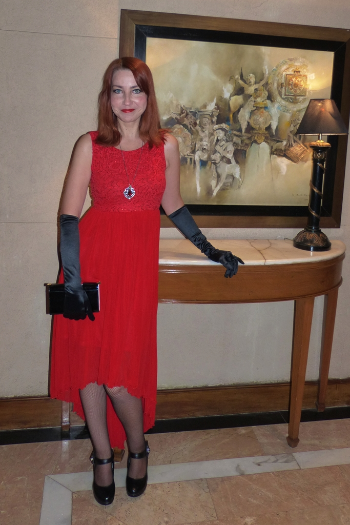 New Year party outfit: red dress with asymmetrical hem, long black gloves, Swarovski pendant
