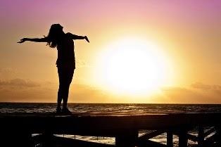 una donna felice a braccia aperte al mare con il sole
