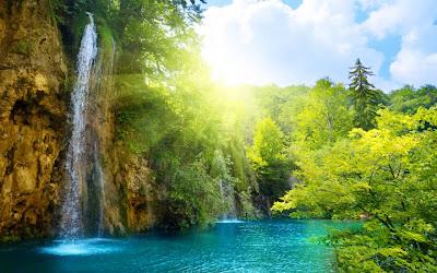 Cascada de agua azul iluminada por el sol