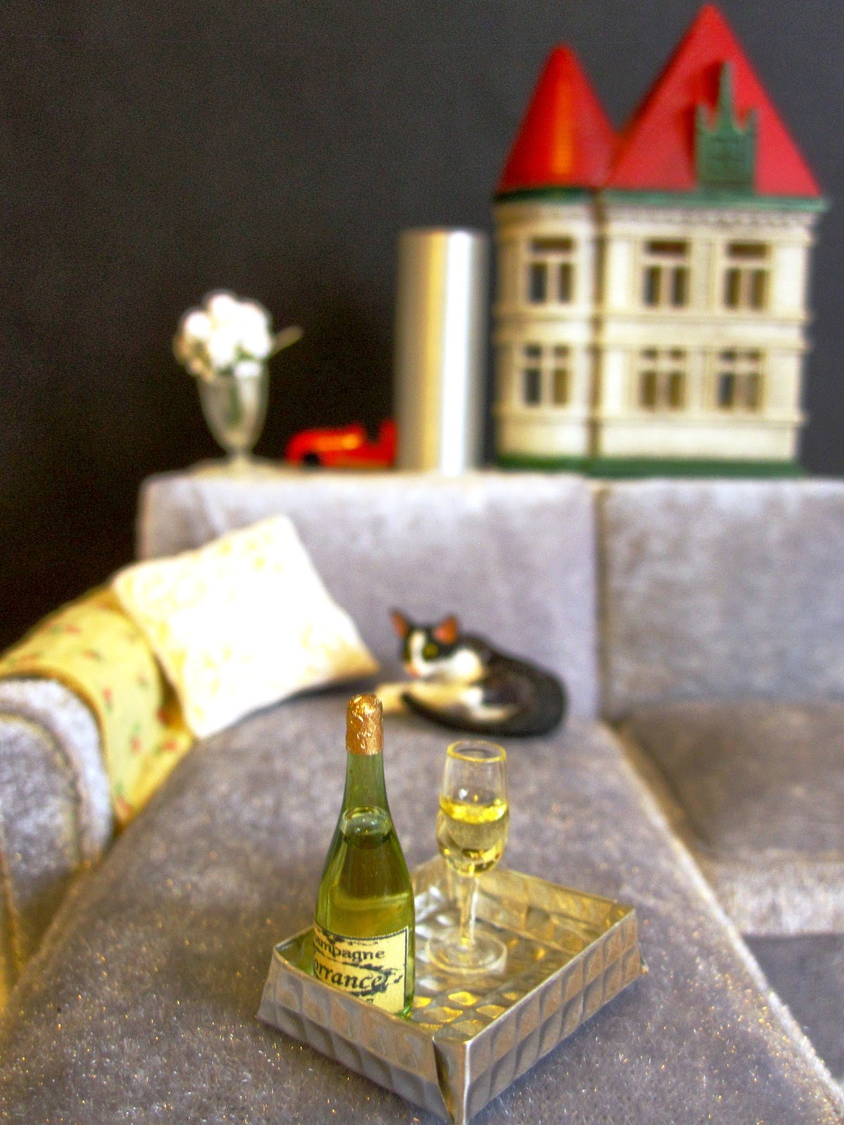 Miniature scene with grey velvet modern miniature chaise sofa, sleeping cat, champagne and miniature dolls house