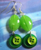 Long drop dangle earrings have layered green buttons hanging from big oval glass beads