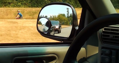 View through driver's side window showing passing vehicles in mirror and bicyclist in distance