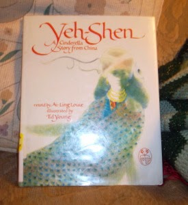 Photo of a book, Yeh-Shen by Ai-Ling Louie, propped against a cushion with a crocheted afghan folded next to it.