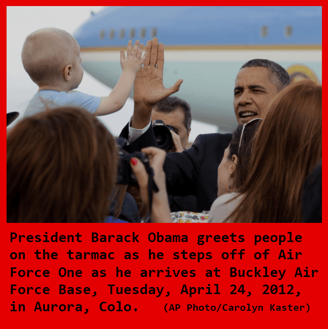 President Barack Obama high fives a young child on the tarmac