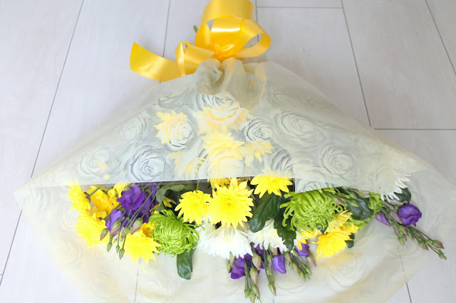 bouquet of yellow white and purple flowers with yellow bow on white wooden floor