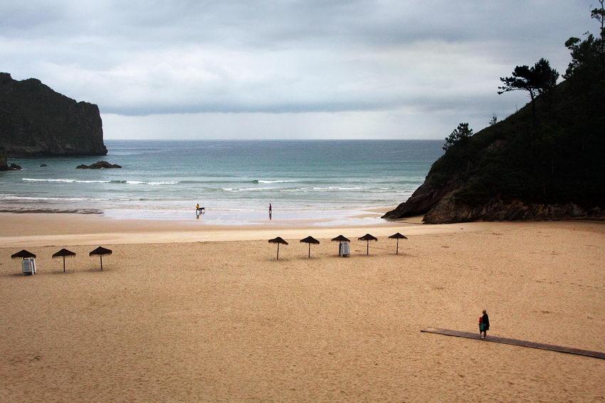 Vista da praia: um passadiço a entrar pela esquerda e uma mulher a caminhar nele e duas pessoas com um cão na areia junto ao mar