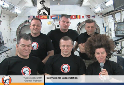 The crew of the International Space Station wearing Yuri's Night T-Shirts send congratulations to all those involved in promoting space exploration. NASA-TV 2011.