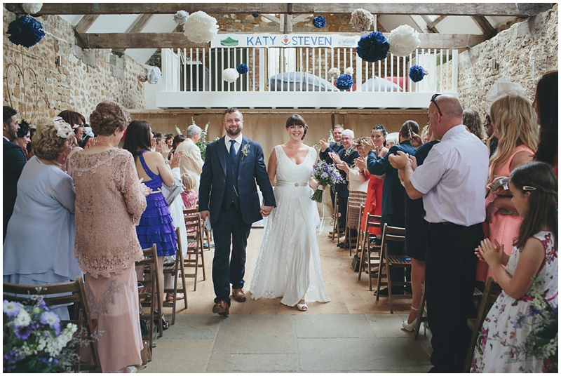 Bride and groom walk down the aisle at the Tithe Barn, Dorset