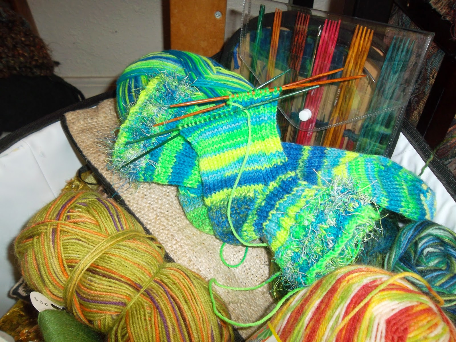 Neon yellow, green and blue-striped socks on double-pointed knitting needles, in a basket with other skeins of yarn and a package of double-pointed needles.