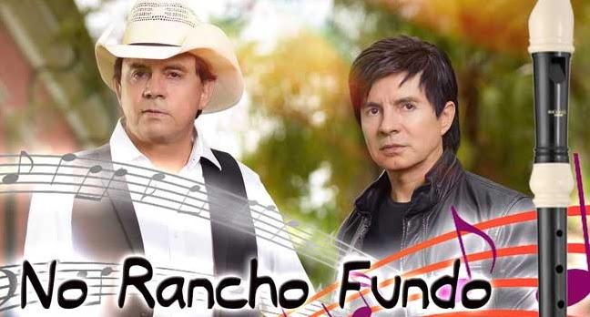 Chitãozinho e Xororó em pose, olhando pra frente. Uma flaut doce ao lado direito. Notas músicais no inferios da imagem e a escrita: no rancho fundo.