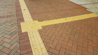 junction on a sidewalk marked with the raised beads and straight lines