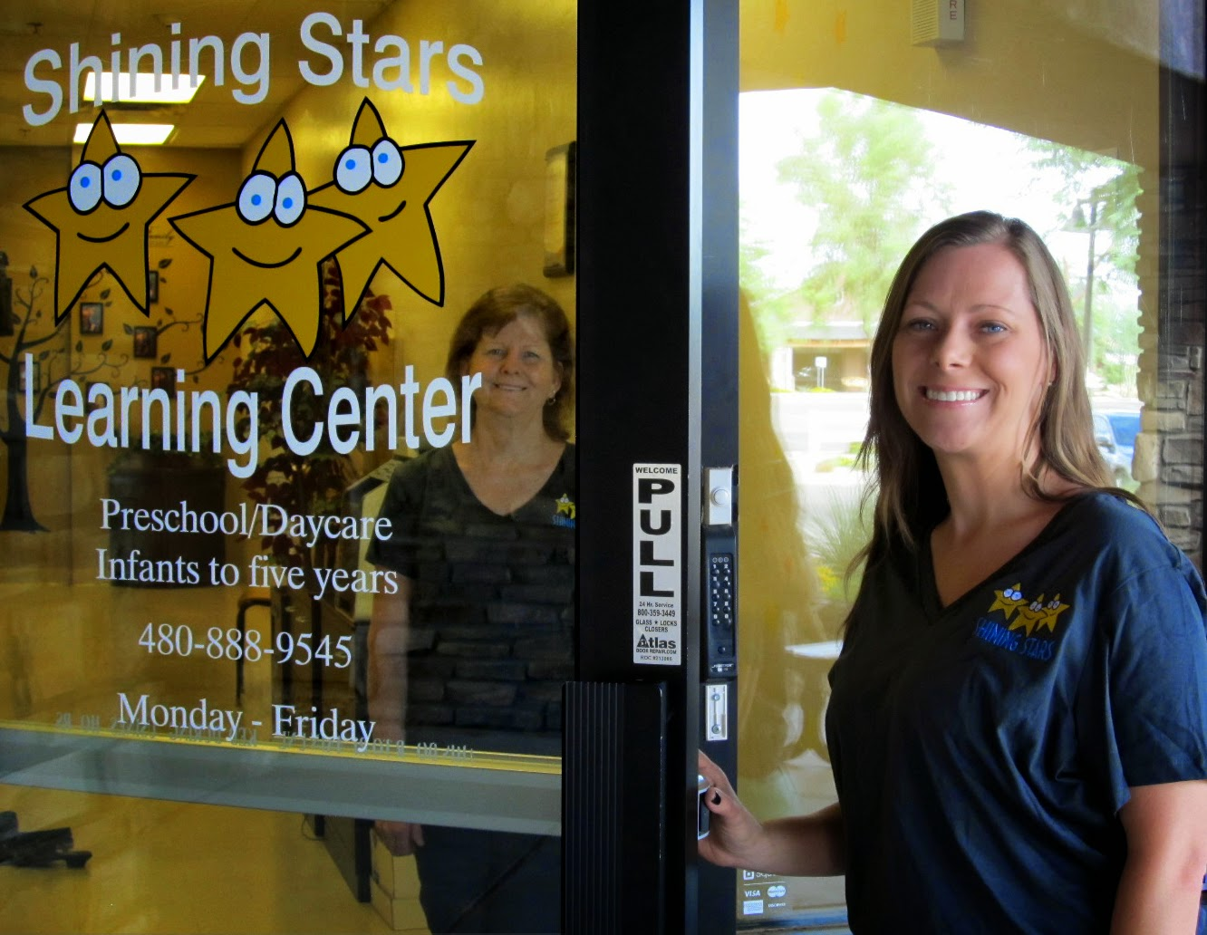 Two women pose for a picture outside of the Shining Star Learning Center building.