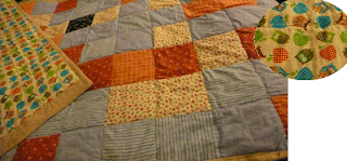 photo of the final quilt, the top corner is turned over to show the reversible underside which is a pattern of owls and apples.