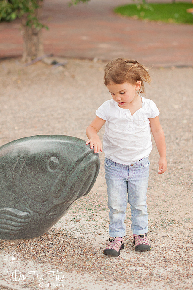 Girl pets fish statue