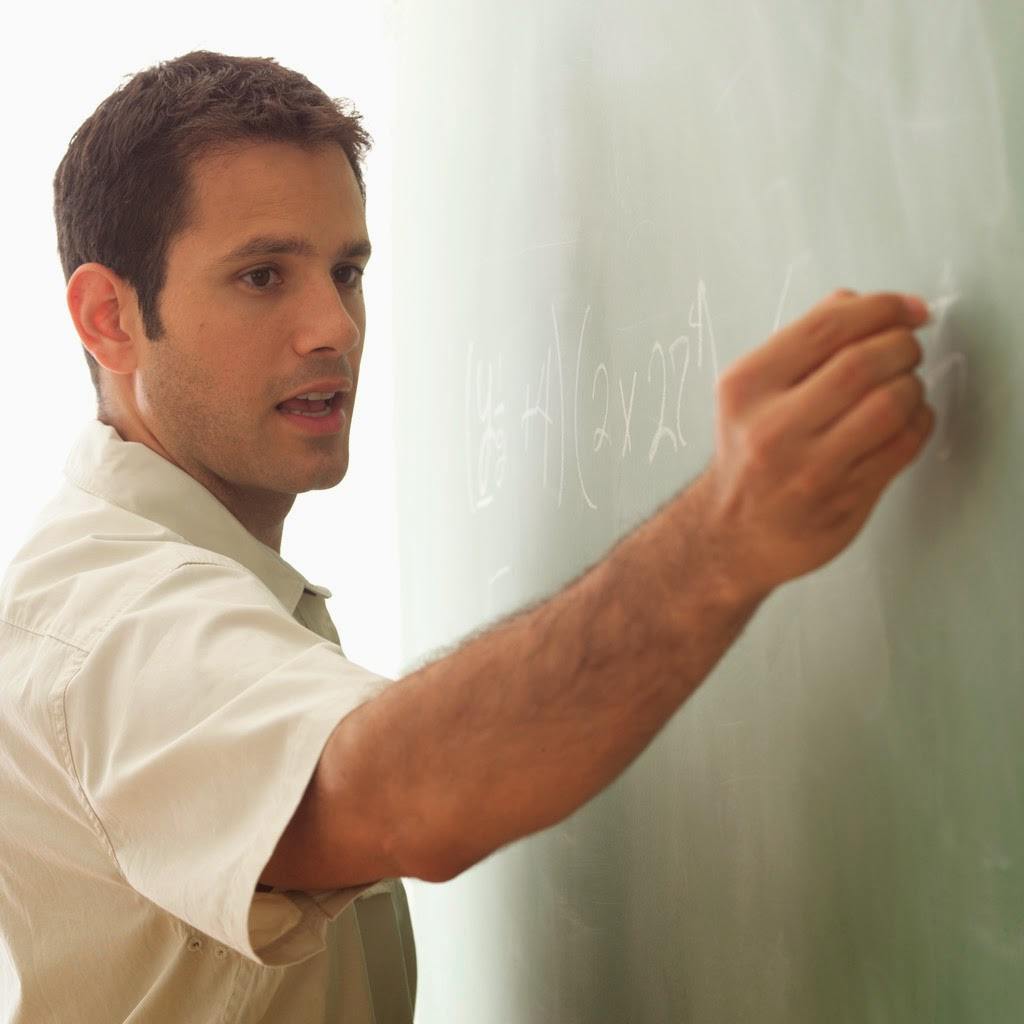 Teacher explaining math on chalkboard.