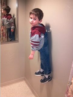 funny picture: child hanging on the coat rack