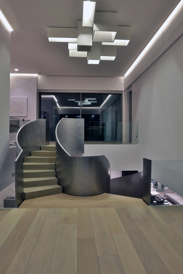 Spiral stairs at night in The Memory House by A-Cero Architects