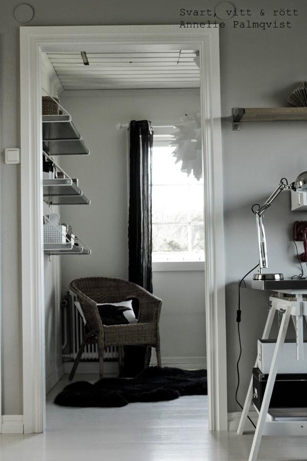 hyllor, ikea hylla, gråmålade väggar, inredning, hall, vitt, svart, trärena detaljer, korgstol, kudde, korp på kudde, kråka, vitt skrivbord, rostfria hyllor, svarta gardiner, balkongdörr, detaljer,