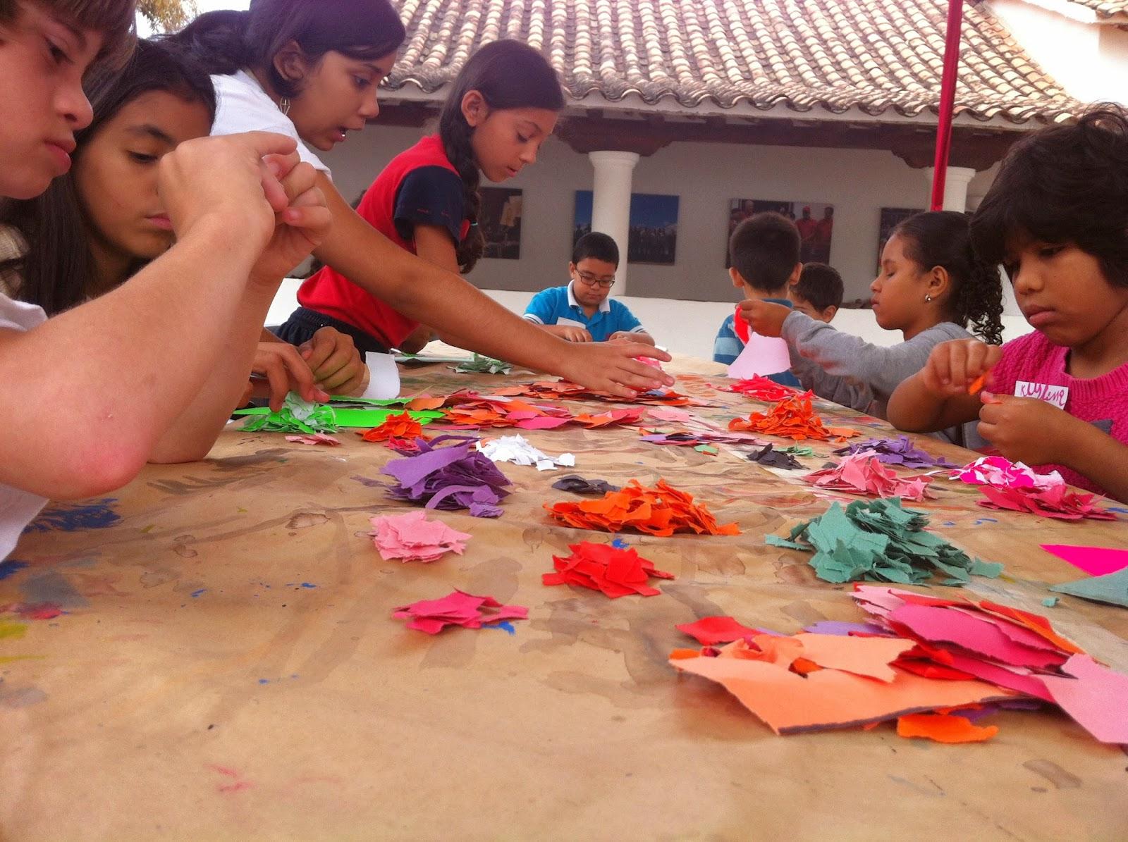 Los niños separan el papel de colores para hacer pulpa