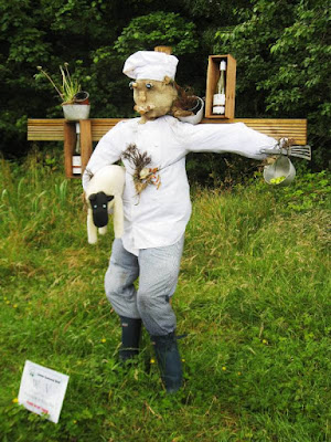 A scarecrow dressed as a chef with a sheep under one arm