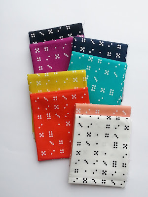 Dotted fabric in a row in rainbow color order featuring a domino dot pattern