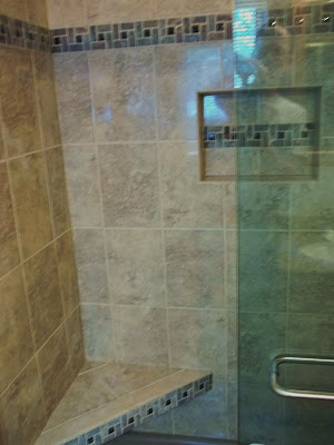 Pinwheel tile accent on seat, niche and walls for shower surround