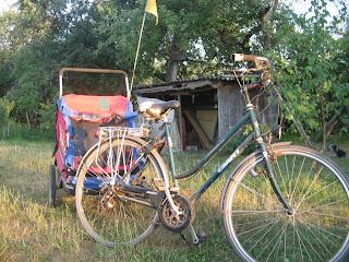 Női trekking bicikli kitámasztva, fél-oldalról látszik. Ehhez utánfutó van csatlakoztatva. Az utánfutó a háttérben látszik, melynek baloldalán hosszú nyélen kis háromszögletű sárga színű figyelmeztető zászlócska van.