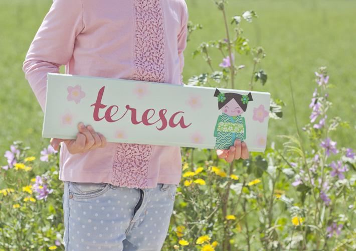 Alicia sotiene un letrero infantil decorado con chalk paint, decoupage y estampación con sellos carvados a mano