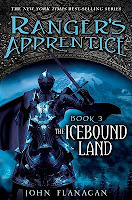 the cover of The Icebound Land by John Flanagan book three in the ranger's apprentice series shows a fully armed knight with sword raised, riding an armored horse with a snowy mountain in the distance