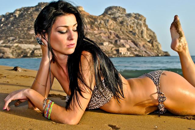 Красивая брюнетка в купальнике лежит на песке
