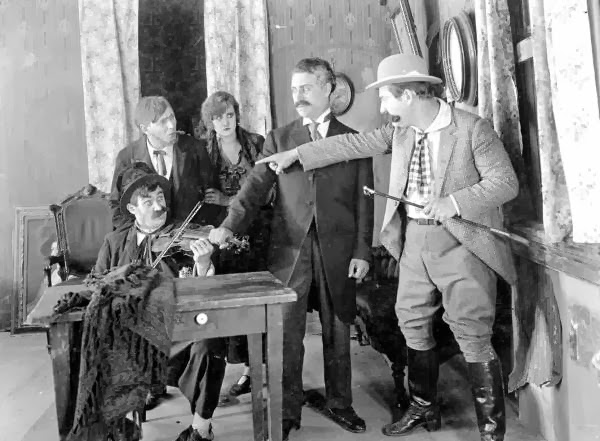 Motion picture scene from Strangled Harmony, 1916.  L-R: Bobby Burns, (?), Ethel Burton Palmer, (?), Walter Stull.