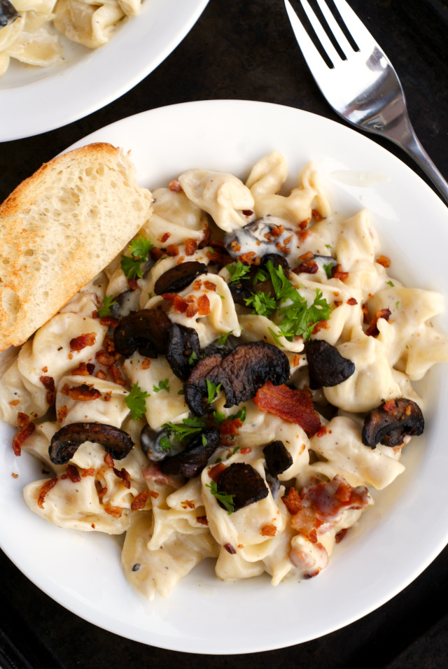 Parmesan Tortellini with Mushrooms and Bacon is a creamy and cheesy pasta dish featuring cheese tortellini swimming in a rich parmesan sauce tossed with caramelized mushrooms and smoky bacon.