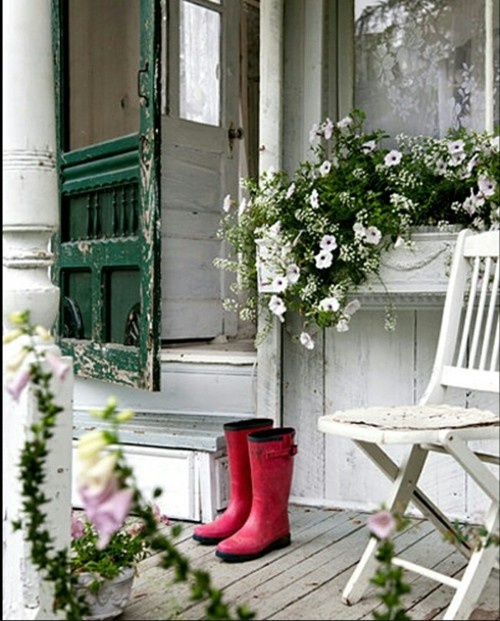 This small porch still has room for rustic farmhouse decor and lush greenery and flower beds