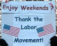 sign with 2 American flags saying, Enjoy weekends?  Thank the labor movement.