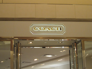The Coach logo over the Coach store.