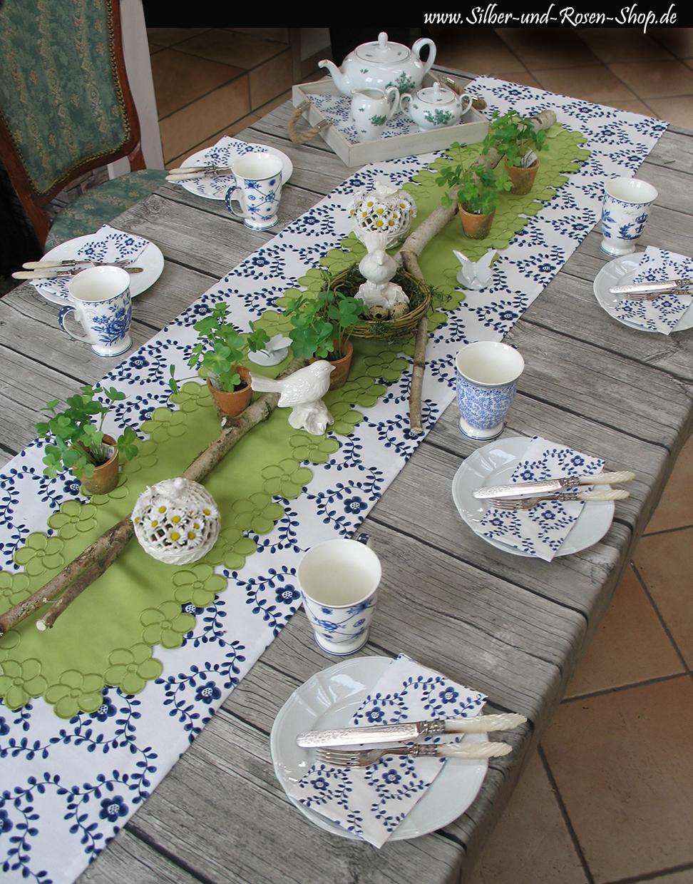 Unterlage ist eine Planken-Wachstuchtischdecke, darüber der Tischläufer Ängsruta (handgenäht bei Silber-und-Rosen-Shop). Dazu ein grüner Tischläufer, künstliche Kleetöpfchen und weiße Porzellandeko. Alles von www.Silber-und-Rosen-Shop.de