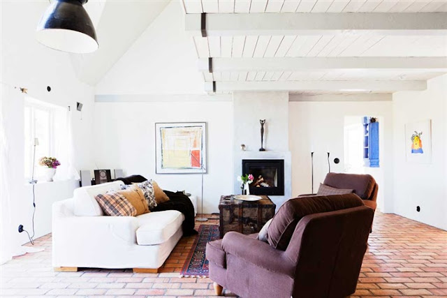 living room inside a converted barn features brick floors, wood ceilings, exposed beams, and a modern fireplace mantel