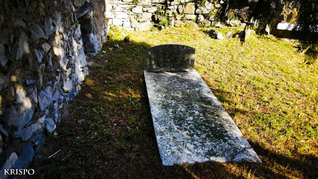 lápida antigua sobre hierba en cenmenterio
